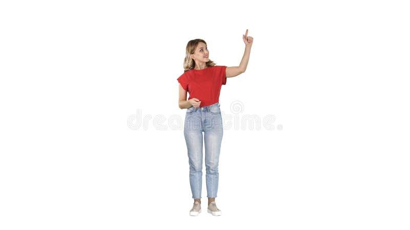 Lächelnde Frau in der zufälligen Kleidung, die etwas, eingebildete Knöpfe auf weißem Hintergrund betätigend darstellt lizenzfreies stockbild
