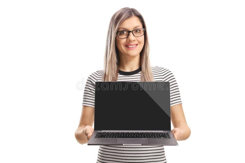 Lächelnde junge Frau, die eine offene Laptop-Computer beschuht stockbild