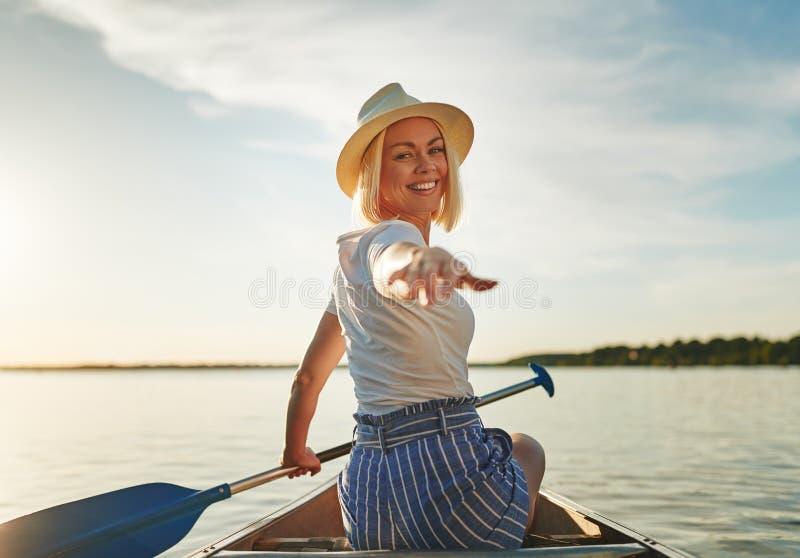 Lächelnde junge Frau, die einen sonnigen Tag canoeing ist im Sommer genießt stockfotografie