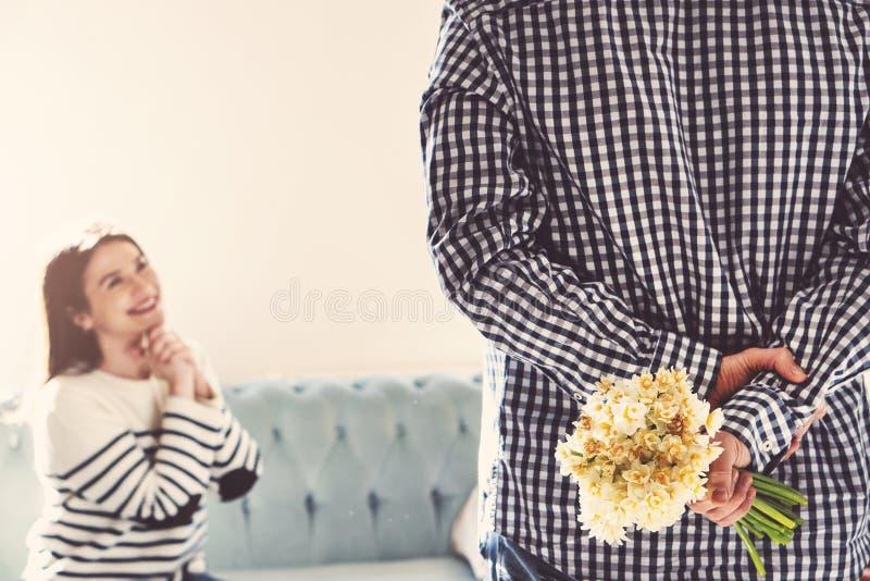 Lächelnde junge Frau, die weiße Narzisse als Liebesgeschenk von ihrem Freund empfängt stockfotografie