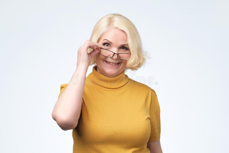 Lächelnder Glas-Kopfschuß der attraktiven älteren Geschäftsfrau tragender lizenzfreie stockbilder
