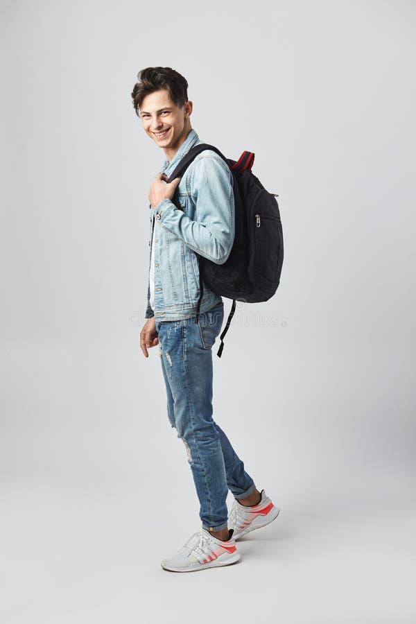 Lächelnder junger dunkelhaariger Kerl mit schwarzem Rucksack auf seiner Schulter gekleidet in einem weißen T-Shirt, in den Jeans  stockfotografie