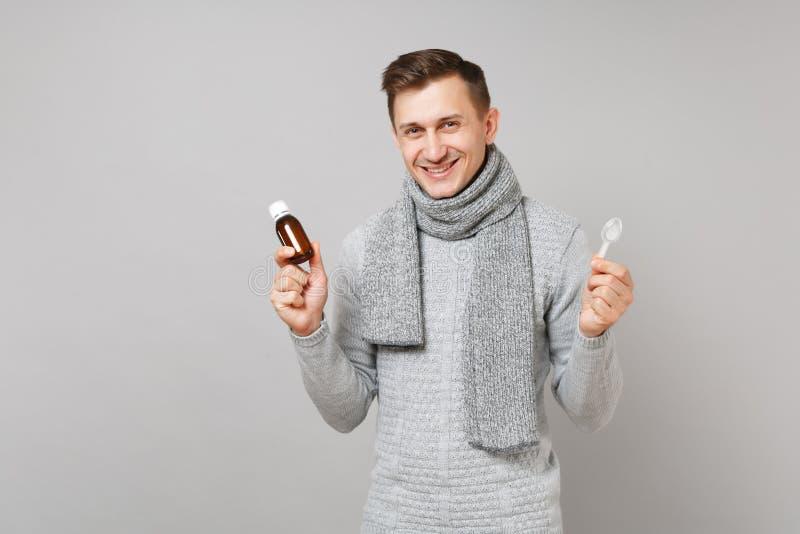 Lächelnder junger Mann in der grauen Strickjacke, Schalgriff gießen flüssige Medizin in Flasche, Löffel auf grauem Hintergrund lizenzfreie stockfotografie