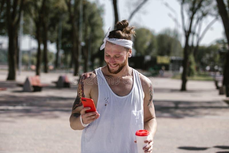 Lächelnder junger Mann mit weißem Stirnband kleidete in einem weißen T-Shirt unter Verwendung des Handys an und hält eine Plastik lizenzfreies stockbild