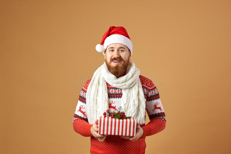 Lächelnder rothaariger Mann mit dem Bart gekleidet in einer roten und weißen Strickjacke mit Rotwild, in einem weißen gestrickten lizenzfreie stockfotografie