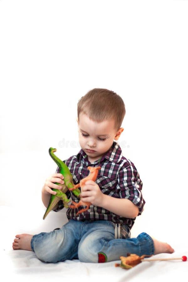 Lächelndes Baby, das mit den Spielwaren lokalisiert auf weißem Hintergrund spielt lizenzfreies stockfoto