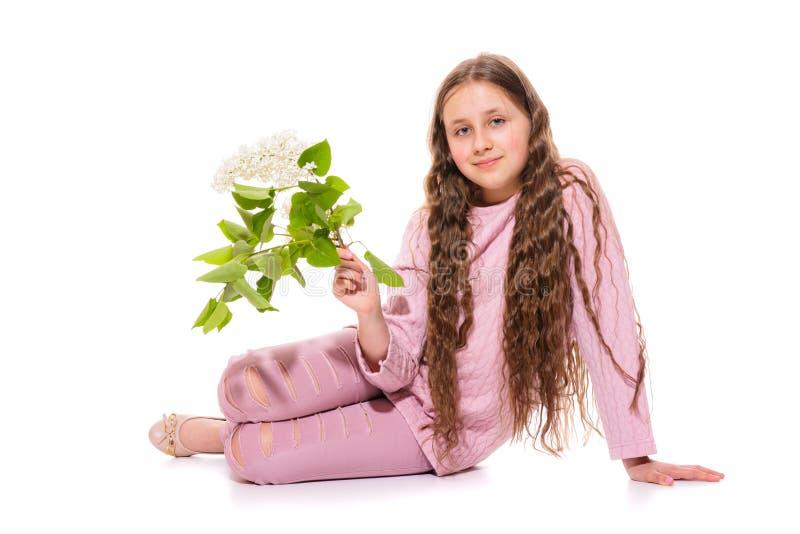 Lächelndes Mädchen 10-11 Jahre alt in einer rosa Klage, die weiße Flieder in ihren Händen hält Isolierung auf einem Weiß stockfoto