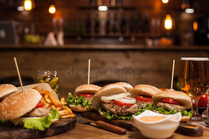 Lód - zimny piwo obok różnorodność hamburgerów w rocznik restauracji fotografia royalty free