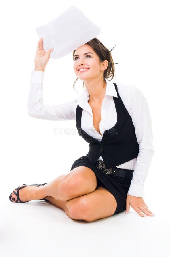 Lächeln der jungen Frau, das auf dem Fußboden mit docume sitzt lizenzfreie stockfotos