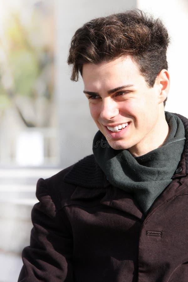 Lächeln des Jungen im Freien mit Mantel und Schal lizenzfreie stockfotografie