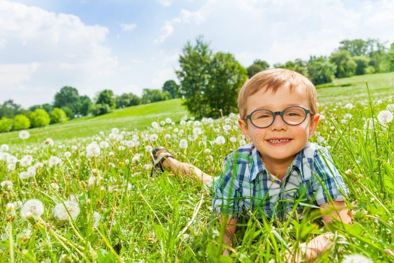 Lächeln des kleinen Jungen, das auf ein Gras legt stockfotos