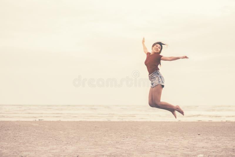Lächeln Frauen und springen auf den Strand stockfoto