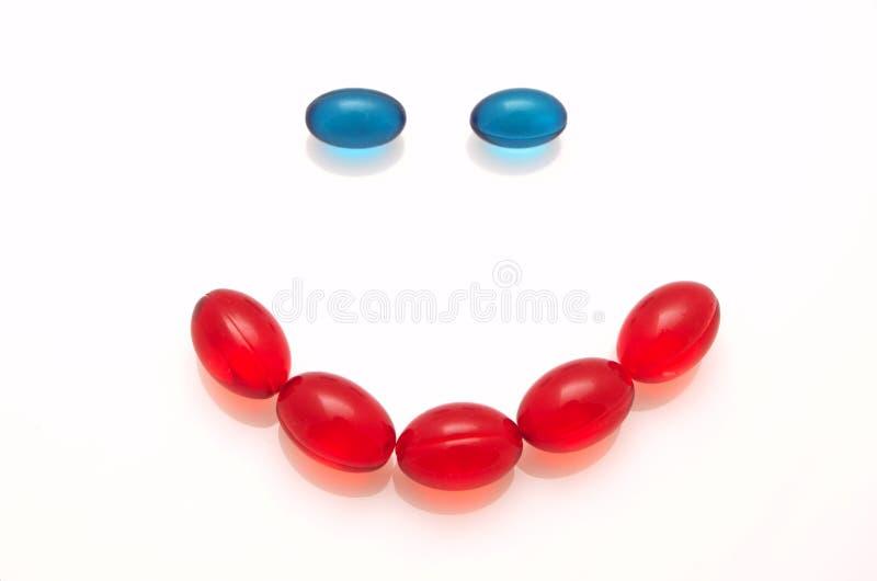 Lächeln gebildet von den blauen und roten Kapseln stockfotos