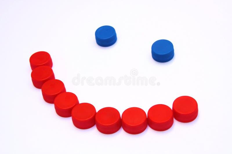 Lächeln gemacht mit HAUSTIER-Deckeln von alkoholfreien Getränken lizenzfreies stockbild