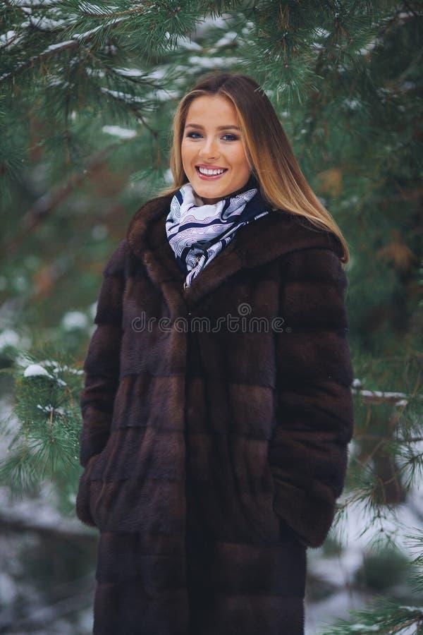Lächeln, glückliches junges Mädchen, das in Winterwald geht stockfoto