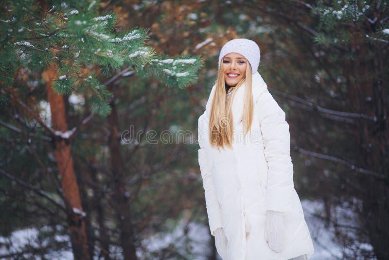 Lächeln, glückliches junges Mädchen, das in Winterwald geht lizenzfreies stockbild