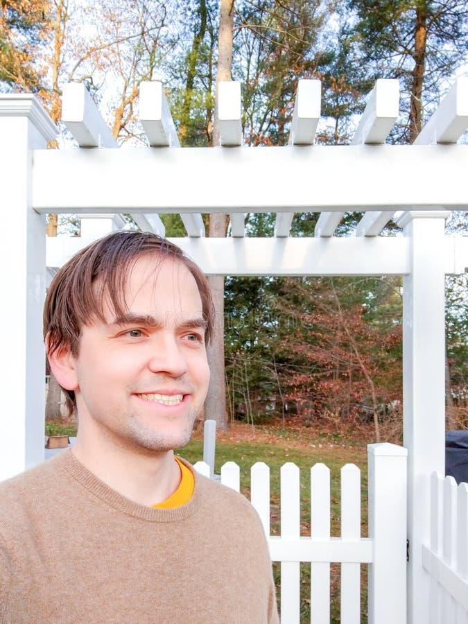 Lächeln in Gruß stehen vor White Picket Zaun am Herbsttag, locker gekleidet lizenzfreies stockbild