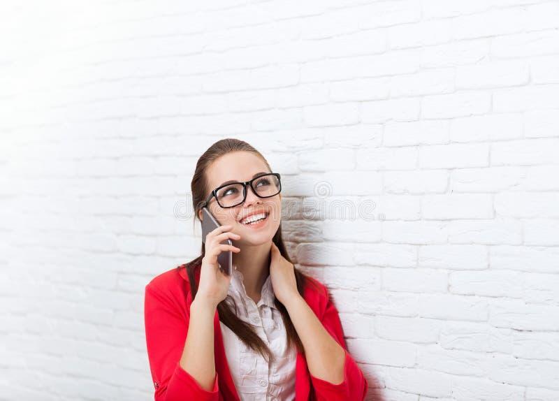 Lächeln-Handyanruf-Problemabnutzung der Geschäftsfrau schauen die roten Jackengläser der glücklichen, die auf beweglichem spreche lizenzfreie stockfotos