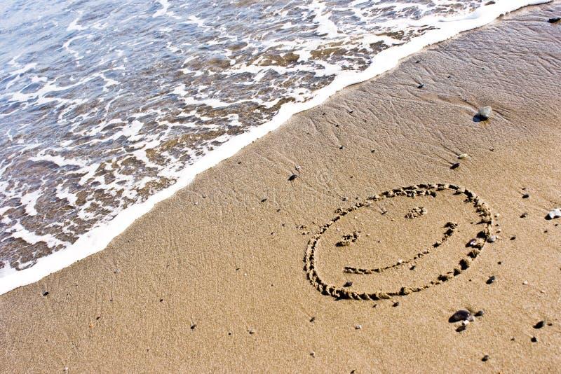 Lächeln im Sand stockbilder