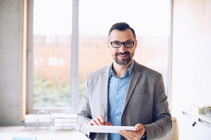 Lächeln 40 Jahre alte hübsche Geschäftsmann, die an Laptop-Computer im Büro arbeiten stockbilder