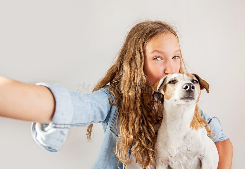 Lächeln jugendlich mit dem Hund, der selfie Foto auf Smartphone über nettem Mädchen des weißen Hintergrundes macht lizenzfreies stockfoto