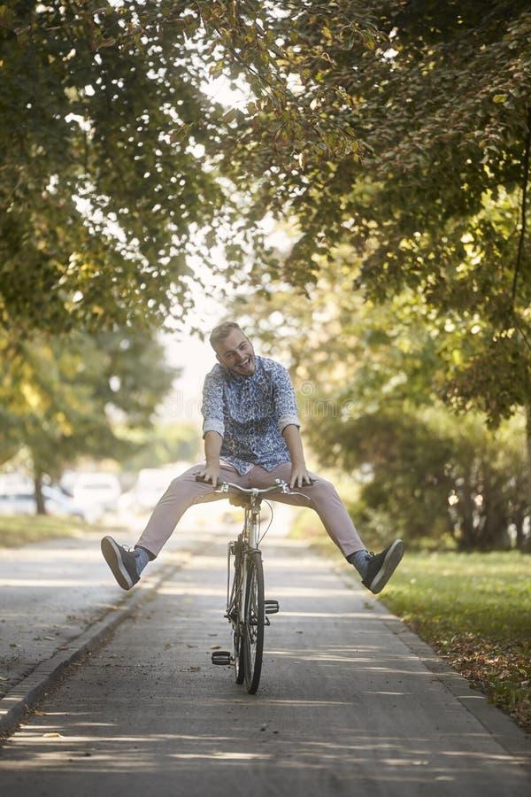 Lächeln, lustiger, lächerlicher, junger Mann, 20-29 Jahre alt, fahrend auf Straßenbahn rad Beinverbreitung stockfoto
