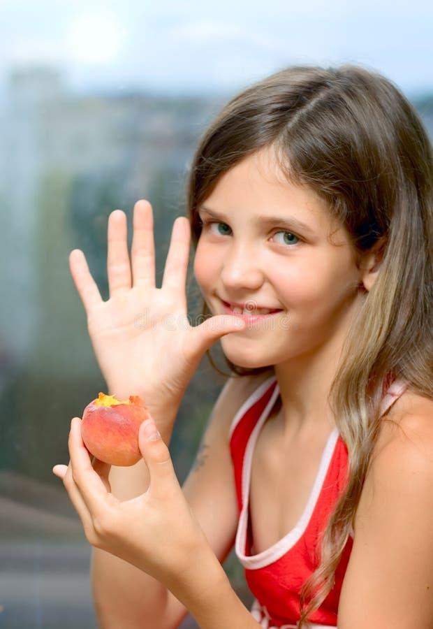 Lächeln-Mädchen essen Pfirsich stockfotos