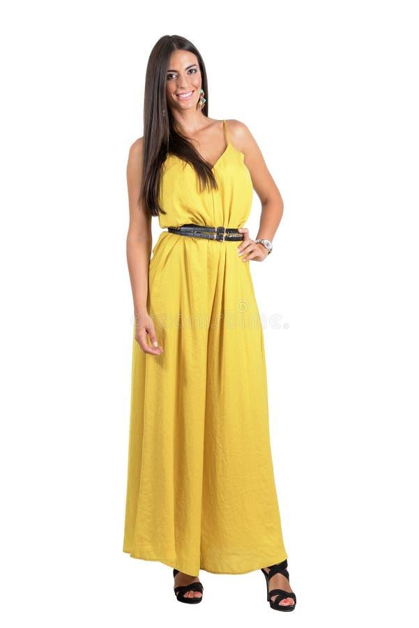 Lächeln, Modeschönheit im gelben Overall mit der Hand auf ihrer Hüfte aufwerfend lizenzfreie stockbilder