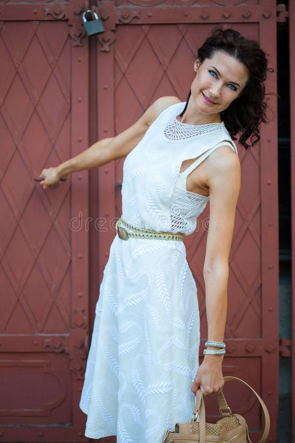 Lächeln recht Frau von mittlerem Alter in einem weißen Kleid mit einer Tasche lizenzfreie stockbilder