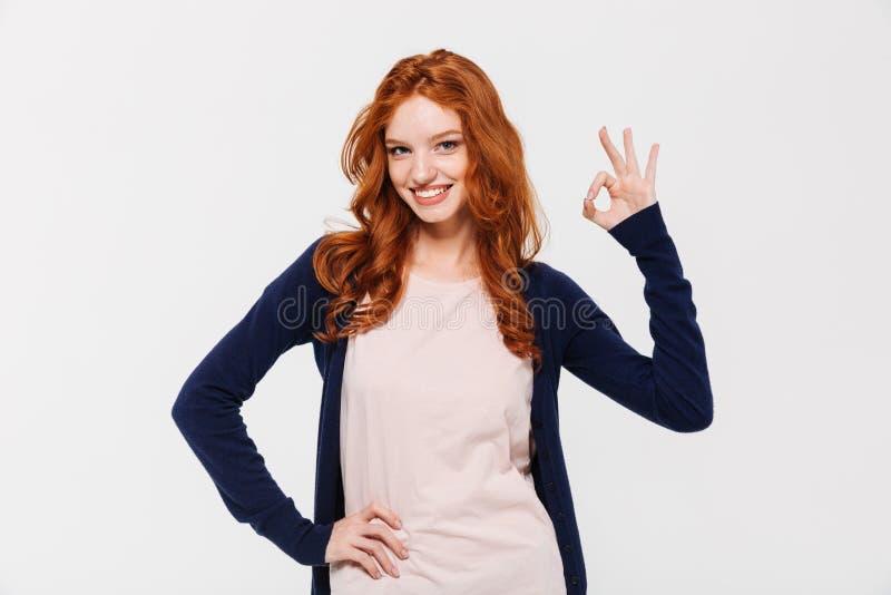 Lächeln recht junge Rothaarigedame, die okaygeste zeigt lizenzfreie stockfotos