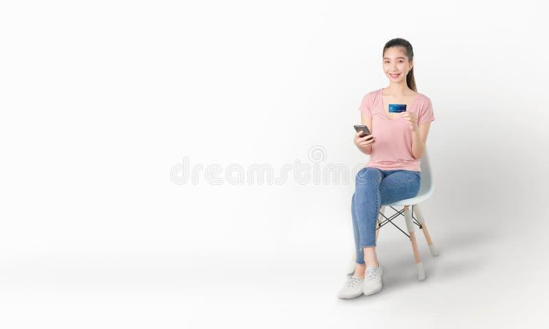 Lächeln Sie glücklich asiatische Frau, die auf dem Stuhl sitzt und Smartphone- und Kreditkarteneinkäufe im Internet auf weißem stockfotografie