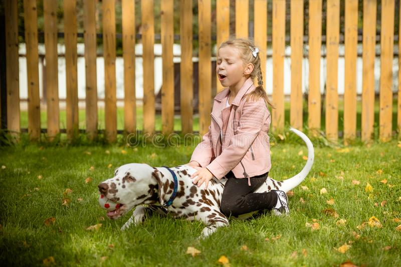 Lächeln, singendes kleines Mädchen, das einen großen Hund in der Wiese, Spiele im Freien umarmt Glückliches Kind liebt ihr Hausti lizenzfreies stockbild