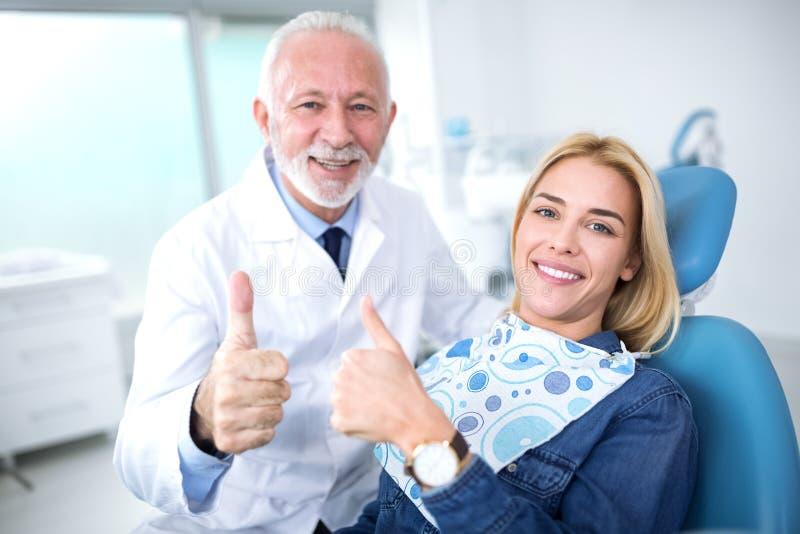 Lächeln und zufriedener erfahrener Zahnarzt und junges geduldiges afte stockbilder