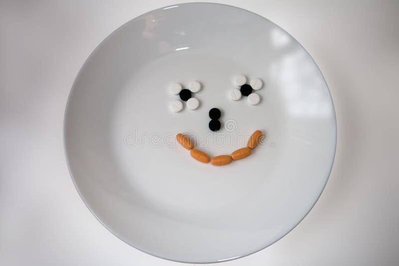 Lächeln von Tabletten auf einer weißen Platte lizenzfreies stockfoto