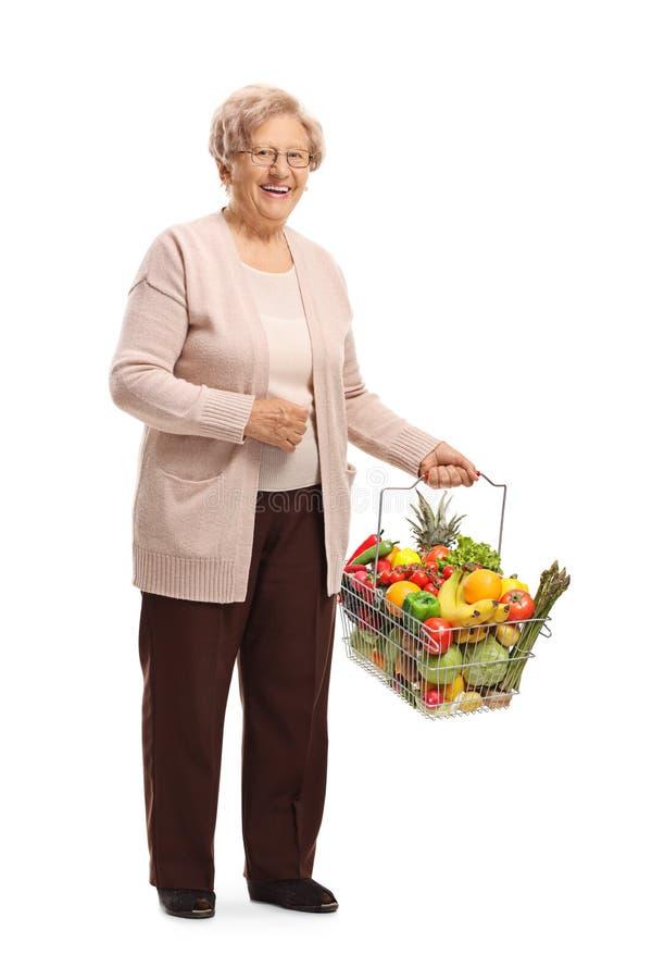 Lächelnde ältere Dame mit einem Einkaufskorb voll von Lebensmittelgeschäften lizenzfreie stockbilder