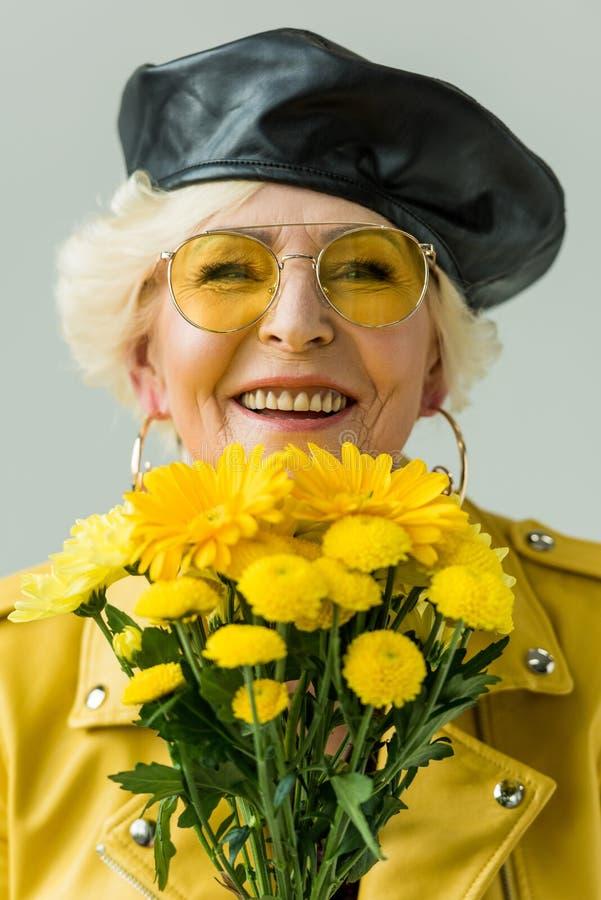 lächelnde ältere Frau in der gelben Lederjacke mit Blumenstrauß von gelben Blumen, stockbild