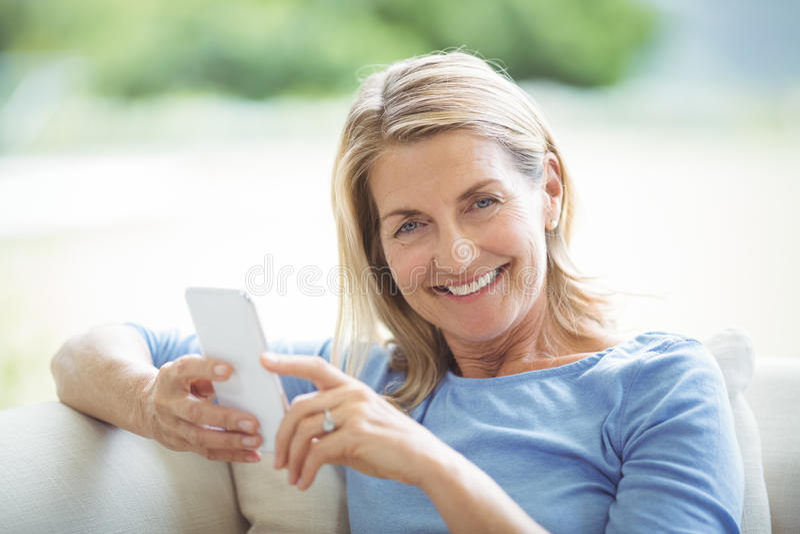 Lächelnde ältere Frau, die Handy im Wohnzimmer verwendet lizenzfreies stockfoto
