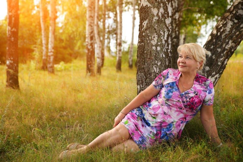 Lächelnde ältere Frau, die im Park sitzt lizenzfreies stockfoto