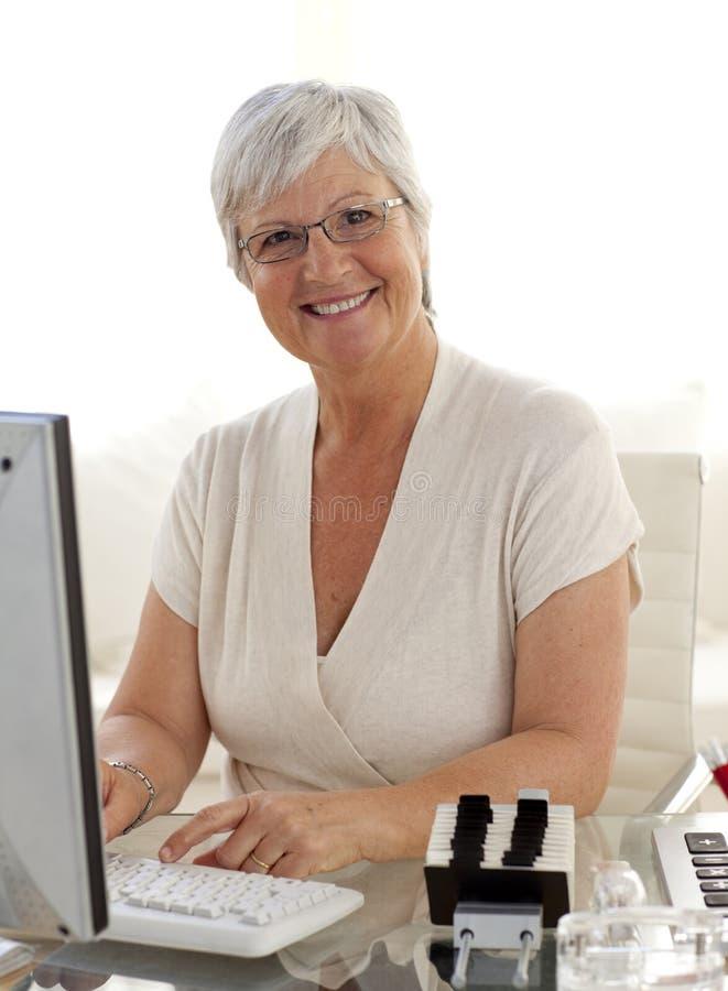 Lächelnde ältere Frau, die mit einem Computer arbeitet stockfotografie
