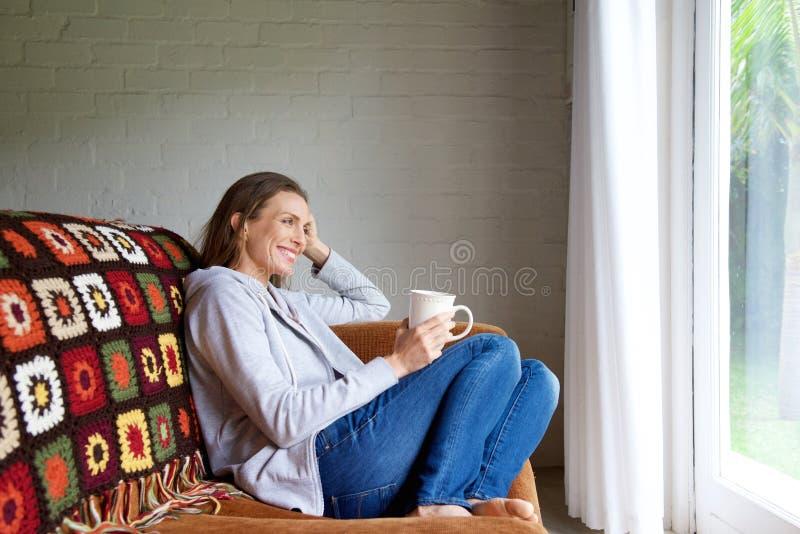 Lächelnde ältere Frau, die sich zu Hause mit Tasse Tee entspannt lizenzfreie stockfotografie