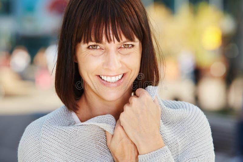 Lächelnde ältere Frau, die weiche Strickjacke hält lizenzfreies stockfoto