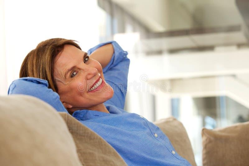 Lächelnde ältere Frau, die zu Hause auf Sofa sitzt stockbilder