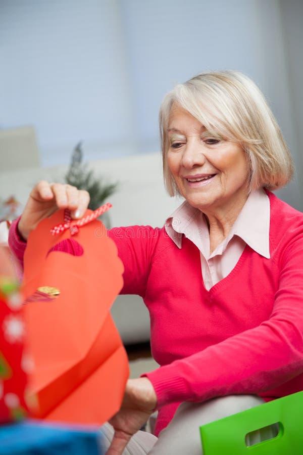 Lächelnde ältere Frau, die zu Hause in der Tasche schaut lizenzfreie stockfotos