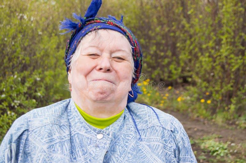 Lächelnde ältere Frau in einem Kopftuch in Ihrem Garten lizenzfreie stockfotos