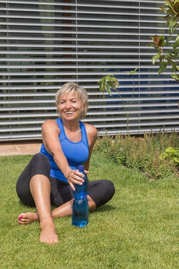 Lächelnde ältere Frau ist entspannend, nachdem sie trainiert hat stockbild