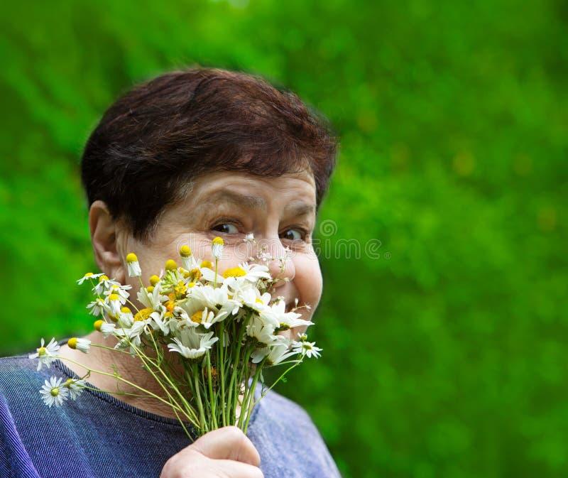 Lächelnde ältere Frau mit Feldblumen lizenzfreie stockbilder