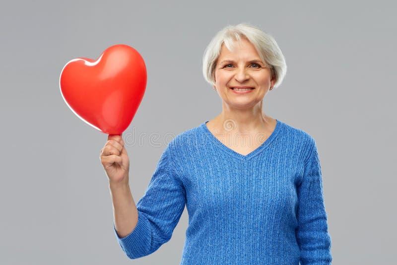 Lächelnde ältere Frau mit geformtem Ballon des roten Herzens lizenzfreie stockfotos