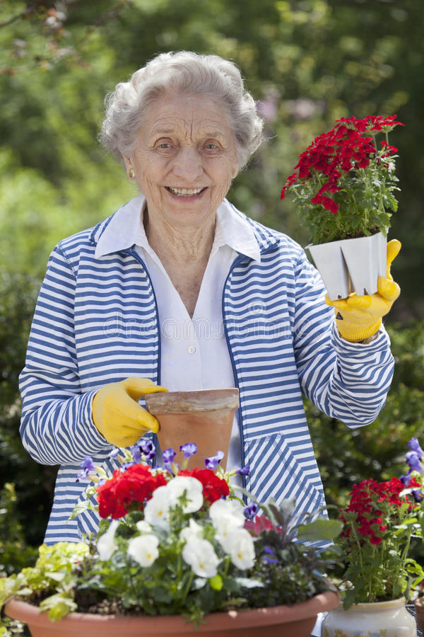 Lächelnde ältere Frauen-Holding-Blumen lizenzfreie stockfotos