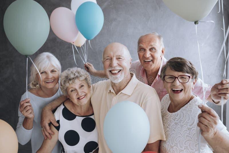 Lächelnde ältere Freunde mit bunten Ballonen das Treffen genießend stockfotos