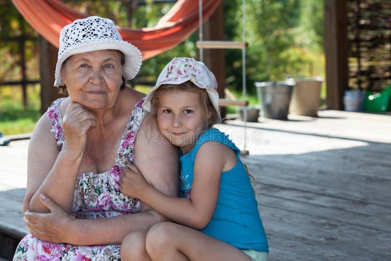 Lächelnde ältere Großmutter und glückliches Enkelkind, die auf Sommerveranda, copyspace umfassen stockfoto